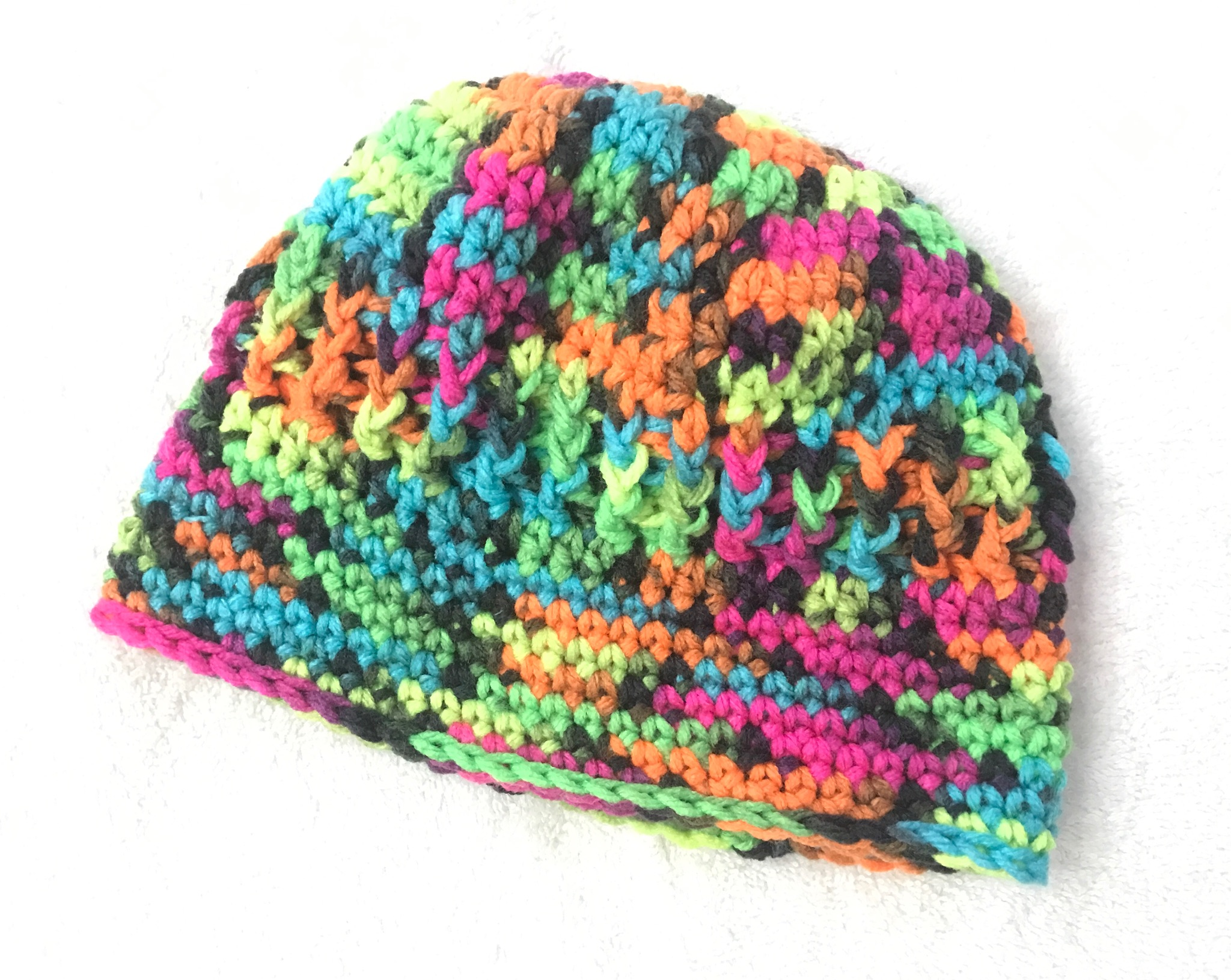 Don't you love the bright colors? What a fun way to use Red Heart Super Saver Blacklight Yarn for this crochet hat.